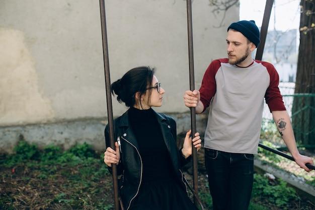 Beau jeune couple posant sur une balançoire