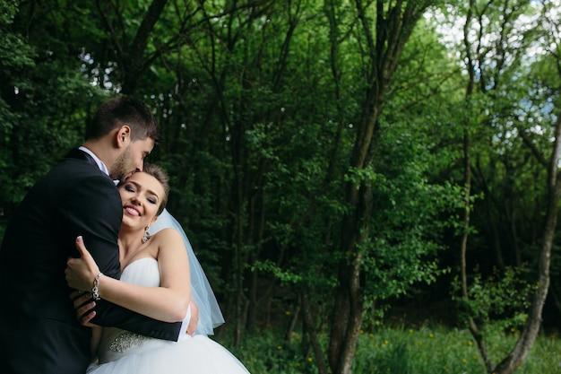 Beau jeune couple posant dans la forêt sous un angle proche