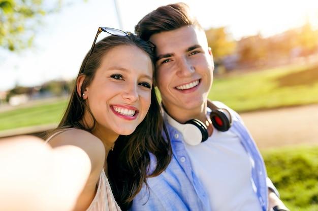 Beau jeune couple prenant un selfie dans le parc.