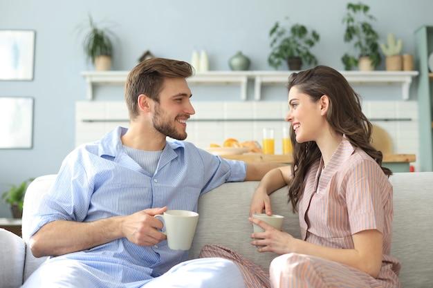 Beau jeune couple en pyjama se regarde et sourit sur un canapé dans le salon.