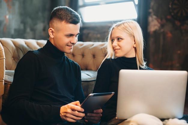 Beau jeune couple à la recherche d'un autre souriant tout en tenant une tablette et un ordinateur portable sur les jambes assis sur le sol à la maison.