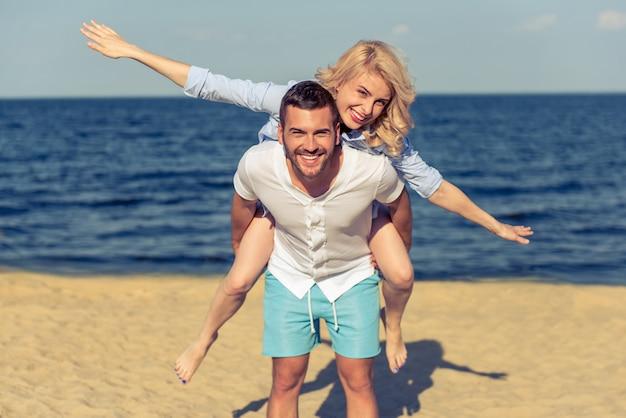 Beau jeune couple regarde la caméra et souriant.
