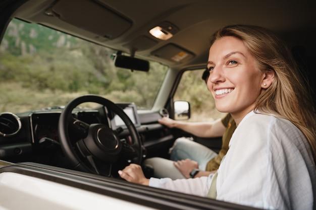 Beau jeune couple souriant assis sur les sièges passagers avant et conduisant une voiture