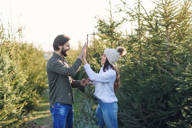 Beau jeune couple souriant élégant se lie avec des fils bel arbre de noël et donnant cinq hauts.