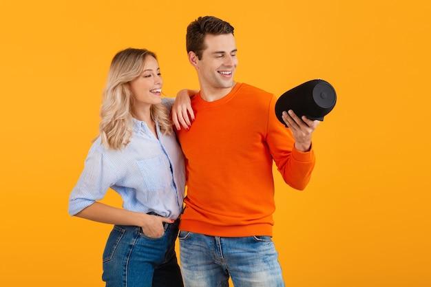 Beau jeune couple souriant tenant haut-parleur sans fil, écouter de la musique sur orange
