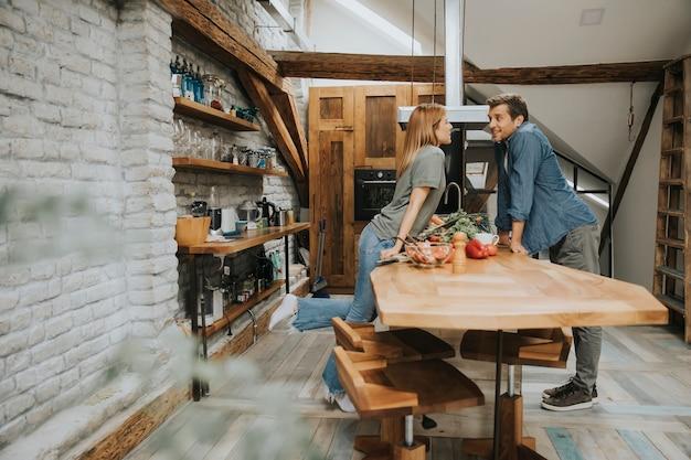 Beau jeune couple souriant tout en cuisinant dans la cuisine à la maison