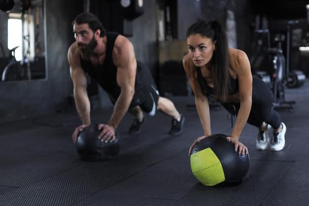 Beau jeune couple sportif indien s'entraîne avec un ballon de médecine dans une salle de sport.