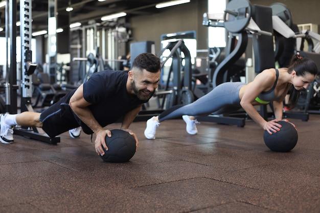 Beau jeune couple sportif travaille avec médecine-ball dans la salle de gym.