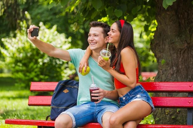 Beau jeune couple tenant des aliments sains prenant autoportrait dans le parc