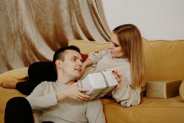 Beau jeune couple tenant une boîte-cadeau alors qu'il était assis sur un canapé à la maison