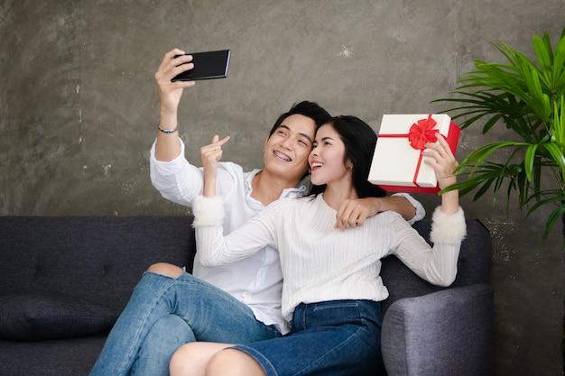 Beau, jeune couple, tenue, cadeau, selfie, sourire, célébrer, maison