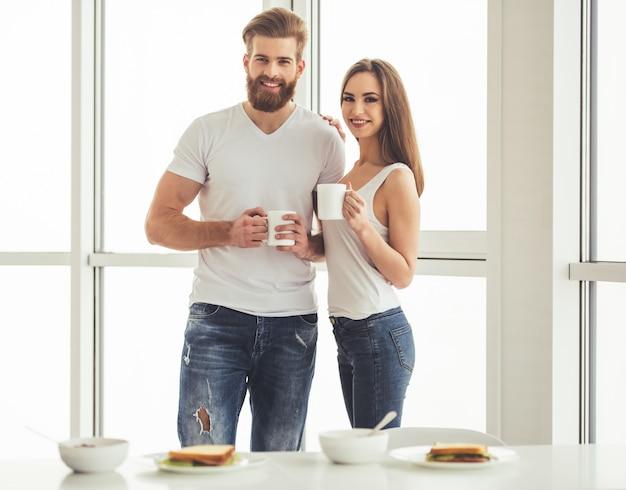 Beau jeune couple tient des tasses.