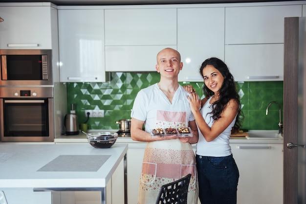 Un beau jeune couple a tracé la palme à la caméra pendant la cuisson dans la cuisine à la maison.