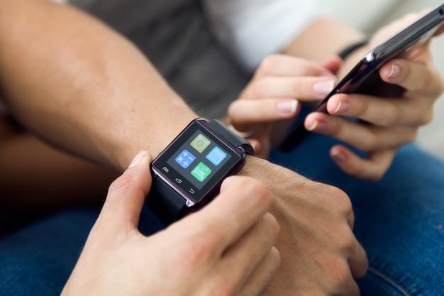 Beau jeune couple utilisant un smartwatch à la maison.