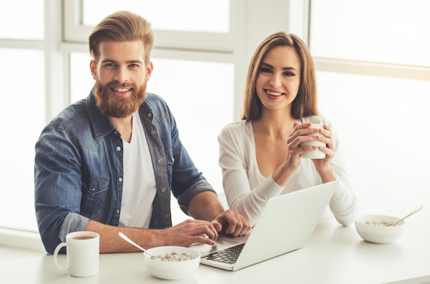 Beau jeune couple utilise un ordinateur portable.