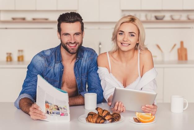 Beau jeune couple utilise une tablette numérique.