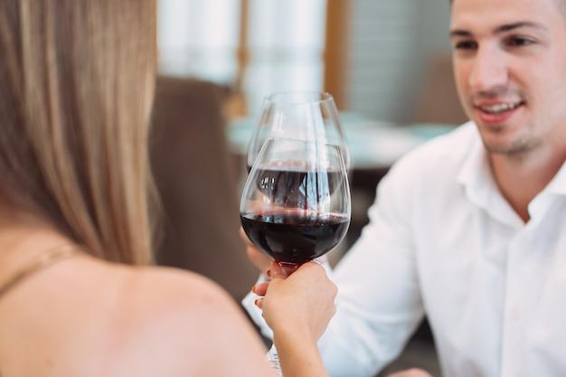 Beau jeune couple avec des verres de vin rouge au restaurant de luxe