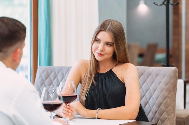 Beau jeune couple avec des verres de vin rouge dans un restaurant de luxe