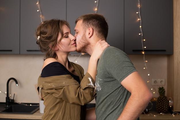 Beau jeune couple en vêtements décontractés s'embrasser et souriant en se tenant debout dans la cuisine à la maison