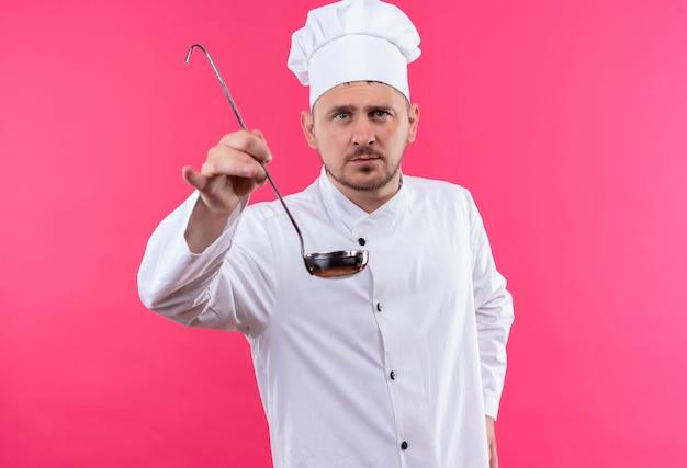 Beau jeune cuisinier en uniforme de chef qui s'étend à la louche à isolé sur l'espace rose