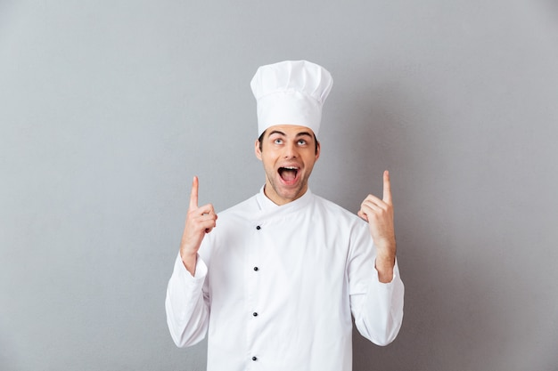 Beau jeune cuisinier en uniforme pointant.