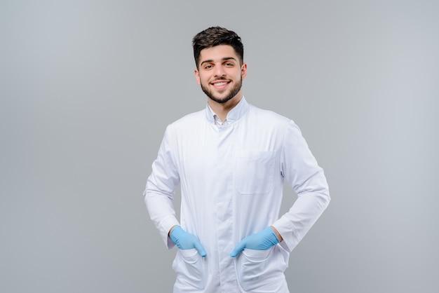 Beau jeune docteur en gants isolé sur gris