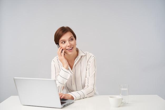 Beau jeune employé de femme brune aux cheveux courts positif ayant une conversation téléphonique et souriant joyeusement tout en posant sur blanc en chemise rayée blanche