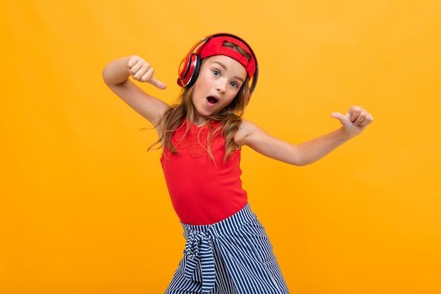 Beau jeune enfant charmant dans un look décontracté avec des écouteurs rouges se détache de la musique et des danses sur un mur orange