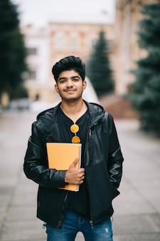 Beau jeune étudiant indien homme tenant des cahiers en se tenant debout dans la rue