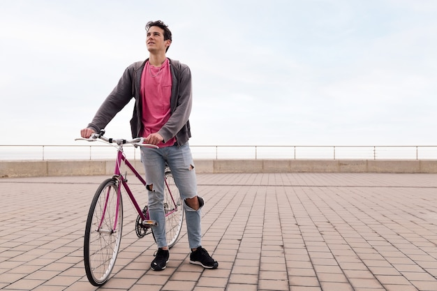 Beau jeune étudiant tenant un vélo vintage