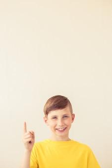 Beau jeune garçon adolescent pointe le doigt vers le haut. espace copie