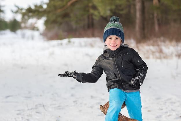 Beau jeune garçon dans la forêt d'hiver.