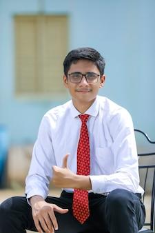 Beau jeune garçon indien portant chemise blanche et cravate rouge
