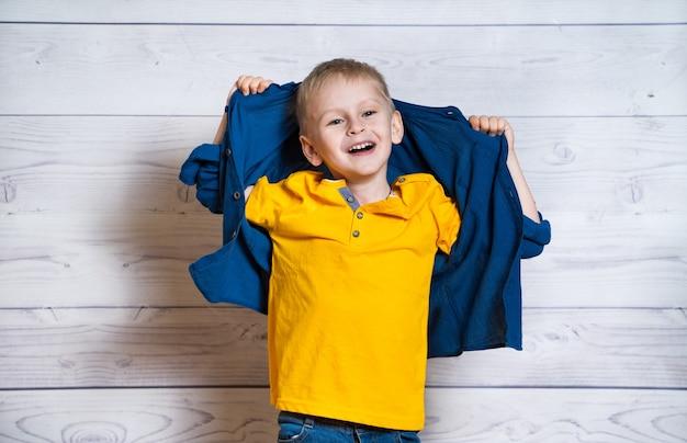 Beau jeune garçon posant à la caméra avec les mains et la veste dans le dos