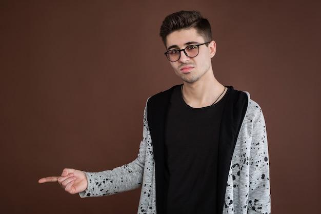Beau jeune homme adulte en chemise regardant la caméra et pointant vers l'extérieur en se tenant debout isolé sur fond marron