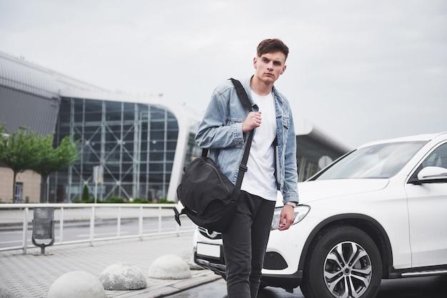 Un beau jeune homme à l'aéroport attend le vol.