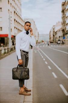 Beau jeune homme d'affaires afro-américain à l'aide d'un téléphone mobile en attendant un taxi en attendant un taxi dans la rue