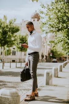 Beau jeune homme d'affaires afro-américain à l'aide d'un téléphone mobile en attendant un taxi dans la rue