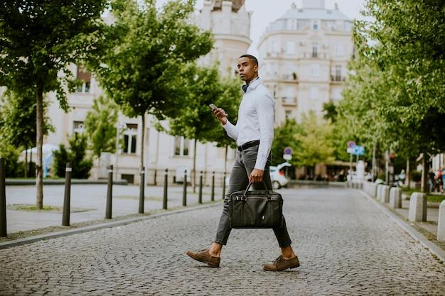 Beau jeune homme d'affaires afro-américain à l'aide d'un téléphone mobile dans une rue