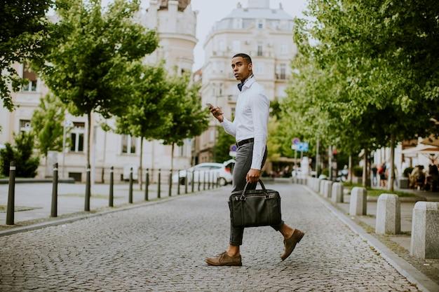 Beau jeune homme d'affaires afro-américain à l'aide d'un téléphone mobile tout en ceossing une rue