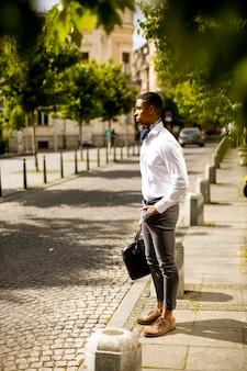 Beau jeune homme d'affaires afro-américain en attente d'un taxi dans la rue