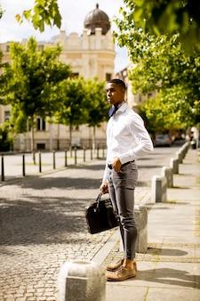 Beau jeune homme d'affaires afro-américain en attente d'un taxi dans une rue