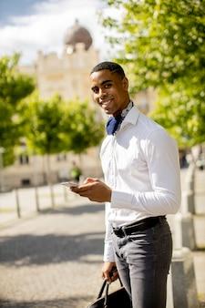 Beau jeune homme d'affaires afro-américain utilisant un téléphone portable en attendant un taxi dans une rue