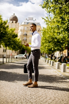 Beau jeune homme d'affaires afro-américain utilisant un téléphone portable dans une rue