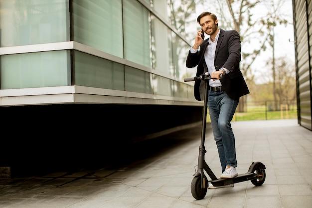 Beau jeune homme d'affaires à l'aide de téléphone mobile sur scooter électrique