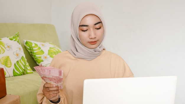 Beau jeune homme d'affaires asiatique calculant le revenu de commande