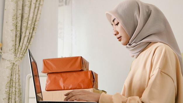 Beau jeune homme d'affaires asiatique prenant soin des commandes avec son ordinateur portable