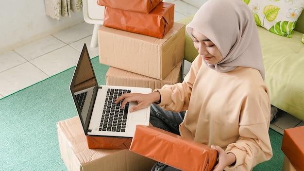 Beau jeune homme d'affaires asiatique préparant les commandes à emballer aux clients