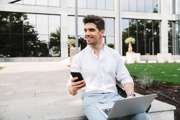 Beau jeune homme d'affaires assis à l'extérieur à l'aide d'un ordinateur portable et d'un téléphone mobile