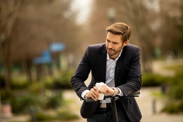 Beau jeune homme d'affaires buvant une tasse de café à emporter sur scooter électrique
